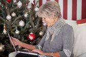 Elderly lady sending Christmas greetings — Stock Photo