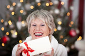 Laughing elderly lady with an Xmas gift voucher — Stock Photo