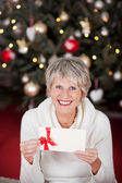 Smiling senior lady with a gift voucher — Stok fotoğraf
