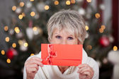 Elderly lady with a red gift voucher — Stock Photo
