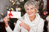 Smiling woman pointing to a Christmas voucher — Stock Photo