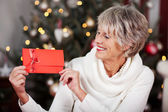 Smiling woman displaying a red Christmas voucher — Stok fotoğraf