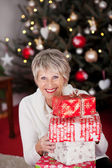 Happy grandmother with Christmas gifts — Stock Photo