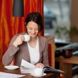 Woman relaxing with coffee and a magazine — Stock Photo