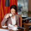 Stock Photo: Womrelaxing with coffee and magazine
