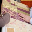 Stock Photo: Womlooking at wallpaper and fabric swatches