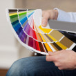 Stock Photo: Man holding a set of paint colour swatches