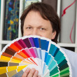 Man matching paint and carpet colours — Stock Photo