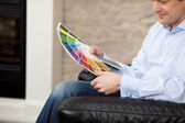 Man in his living room checking paint colours — Stock Photo