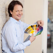Man checking paint colours against a wall — Stock Photo