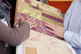 Woman looking at wallpaper and fabric swatches — Stock Photo
