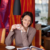 Woman enjoying coffee in a beautiful interior — Stock Photo
