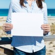 Woman showing white paper standing by the beach — Stock Photo