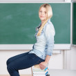 Female Student Sitting On Stack Of Book In Classroom — Stock Photo