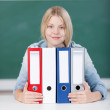 Female Student With Colorful Binders At Desk In Classroom — Stock Photo