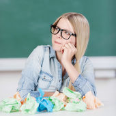 Student With Hand On Chin And Paperballs On Desk — Stock Photo