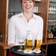 Stock Photo: Laughing bartender serving drinks