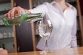 Woman pouring a glass of mineral water — Stock Photo