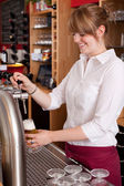 Pretty waitress serving draft beer — Stock Photo