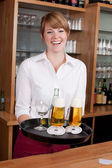 Laughing bartender serving drinks — Stock Photo
