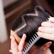 Stock Photo: Hairstylist combing new hairstyle