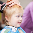 Cute little child getting a haircut — Stock Photo