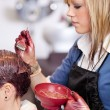 Stock Photo: Young hairdresser applying tint