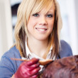 Stock Photo: Smiling hairstylist applying tint