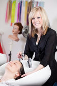 Hairdresser washing a clients hair in the salon — Stock Photo
