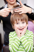 Cute young child at the hairdresser — Stock Photo