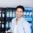 Man Carrying Crate Of Water Bottles In Store — Stock Photo