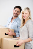 Couple Carrying Cardboard Boxes At Home — Stock Photo