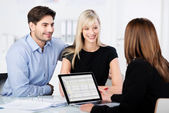 Couple Smiling While Looking At Financial Advisor At Desk — Stock Photo