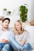 Happy Couple Sitting On Sofa At Home — Stock Photo