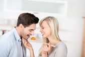 Woman Feeding Food To Man In Kitchen — Stock Photo