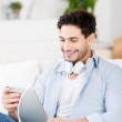 Man With Headphones Using Digital Tablet At Home — Stock Photo