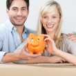 Smiling couple with a piggy bank — Stock Photo