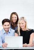Geschäftskollegen Lächeln beim Lesen eines Laptops — Stockfoto