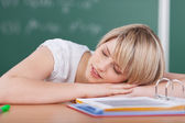 Tired young student sleeping on her books — Stock Photo