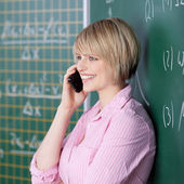 Student chatting on her mobile in the classroom — Stock Photo