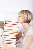 Happy woman with a huge stack of books — Stock Photo