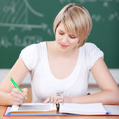 Attractive female student working in class — Stock Photo