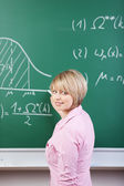 Student or teacher writing on the blackboard — Stock Photo