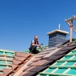 Roofer hammering nails on the beams — Stock Photo
