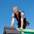 Smiling roofer on top of the roof — Stock Photo