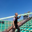 Roofer climbing the roof with a beam — Stock Photo
