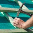Stock Photo: Roofer hammering nail on roof beams