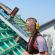 Roofer using safety goggles and ear mufflers — Stock Photo