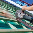 Close-up of roofer using hand circular saw — Stock Photo #28283409