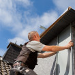 Roofer assemble a metal piece into the dormer wall — Stockfoto